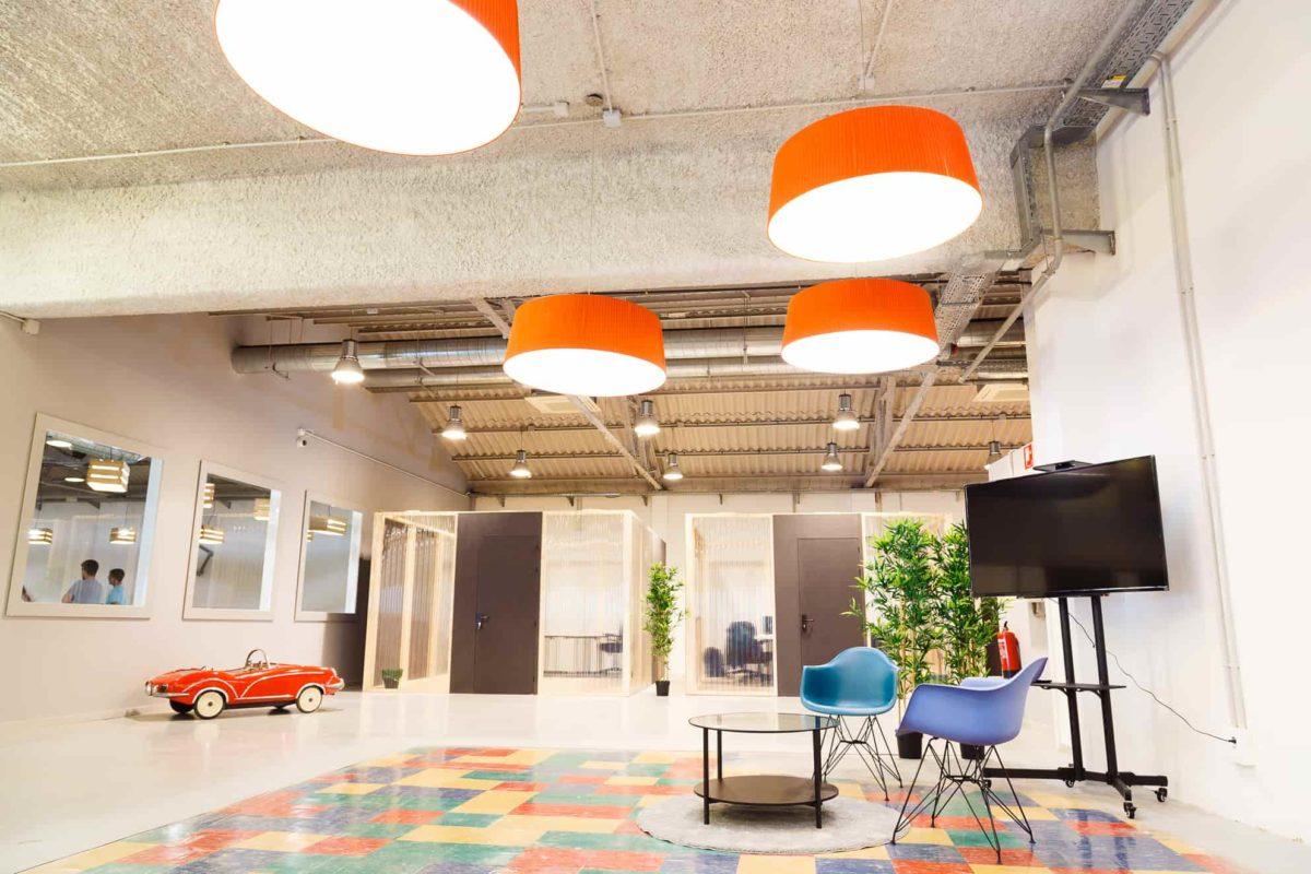 Área de descanso con oficinas al fondo en un coworking de Sabadell